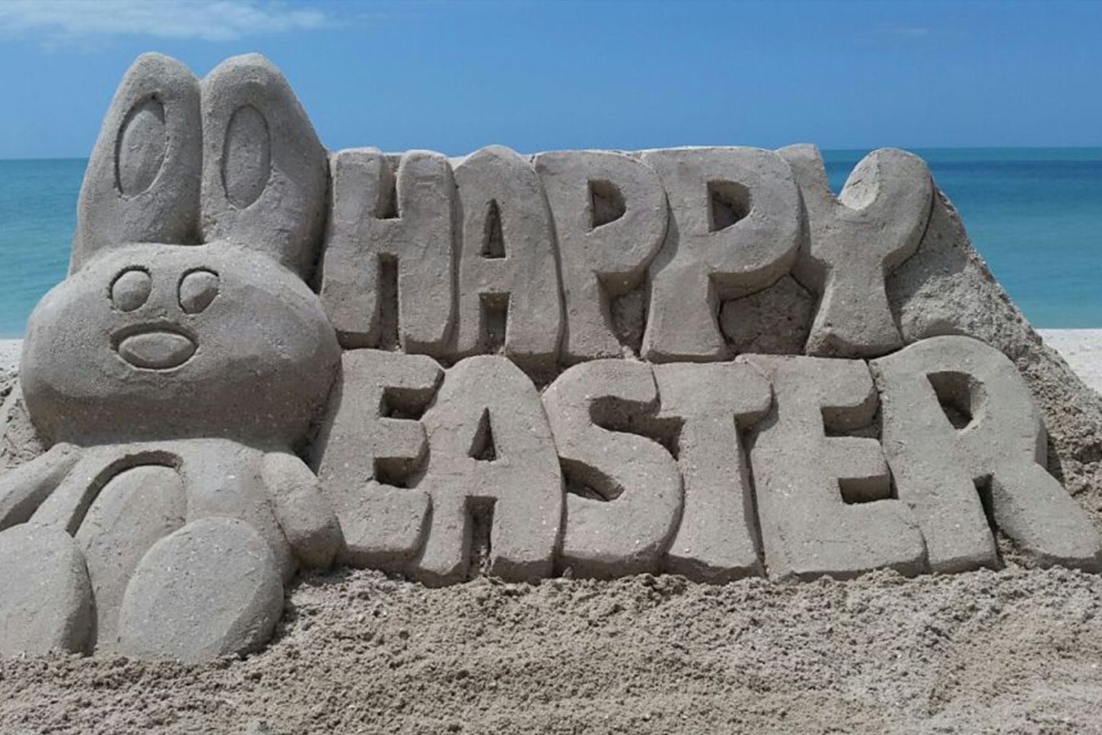Sand sculpture of the words 'Happy Easter' with a bunny